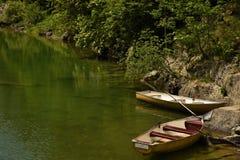 2 шлюпки на береге озера горы стоковая фотография
