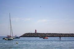 Шлюпки на море и пристани с красным маяком стоковое фото