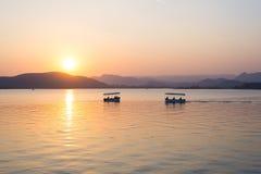 Шлюпки плавая на озеро Pichola с красочным заходом солнца reflated на beyong воды холмы Udaipur, Раджастхан, Индия Стоковое фото RF
