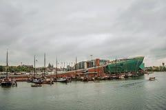 Шлюпки плавая перед музеем и портом науки NEMO на пасмурный день в Амстердаме стоковое фото