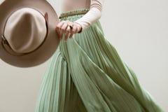 Шляпа, бежевая блузка и юбка pleats бирюзы на светлом backgraund улицы стоковое фото rf