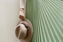 Шляпа, бежевая блузка и юбка pleats бирюзы на светлом backgraund улицы стоковые изображения