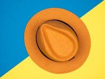 Шляпа в плоском положении на ярких голубых и желтых цветах предпосылки стоковое фото