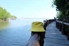 Шляпа желтой женщины на поляке на th мост e деревянный стоковые фотографии rf