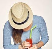 Шляпа женщины нося держа стекло сока смотря вниз Стоковая Фотография