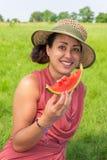 Шляпа женщины нося ест свежую дыню снаружи Стоковые Изображения