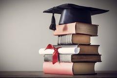 Шляпа и диплом градации с книгой на таблице стоковые изображения