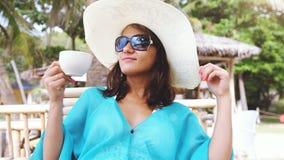 Шляпа и солнечные очки молодой элегантной милой женщины нося на празднике, сидя в кафе пляжа выпивают кофе Стоковая Фотография