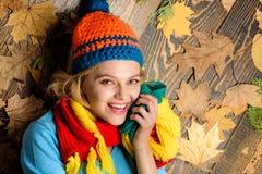 Шляпа и шарф битника связанные женщиной держат листья осени Положение стороны девушки жизнерадостное на деревянной предпосылке с  стоковое фото