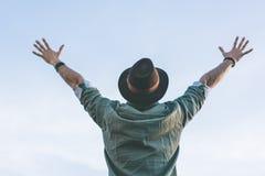 Шляпа моды битника мужская нося, наслаждающся взглядом голубого и ясного неба с подняла его руки вверх Стоковые Изображения RF