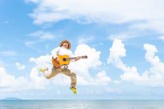 Шляпа пухлого человека нося скача пока играющ гитару стоковая фотография