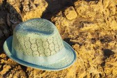 Шляпа ребенк от солнца в форме медведя медведя лежа на утесе на пляже, концепции пляжа стоковые изображения