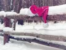 Шляпа Санта Клауса красного цвета на покрытом снег поляке деревянной загородки Стоковые Фото