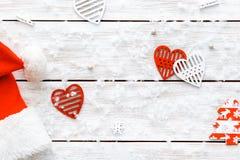 Шляпа Санта Клауса, красные сердца на деревянной белой предпосылке, с Рождеством Христовым карточке дня валентинок, счастливом Но Стоковое фото RF