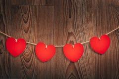 Шнур сердец ` s валентинки влюбленности холстинки естественный и красные зажимы вися на деревенском driftwood текстурируют предпо Стоковая Фотография RF