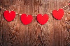 Шнур сердец ` s валентинки влюбленности холстинки естественный и красные зажимы вися на деревенском driftwood текстурируют предпо Стоковая Фотография