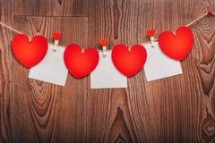 Шнур сердец ` s валентинки влюбленности холстинки естественный и красные зажимы вися на деревенском driftwood текстурируют предпо Стоковые Фотографии RF