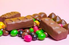 Шоколадные батончики, красочная конфета, помадки на розовой предпосылке стоковое фото rf