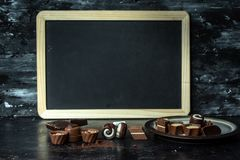 Шоколад любов - различный, сладкие пралине темноты, молоко и белый шоколад на темной, деревянной предпосылке, рядом с доской мела стоковая фотография