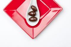 Шоколад покрыл миндалины в белой ложке на красной плите Стоковое Фото