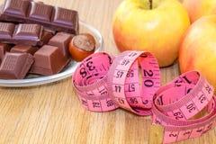 Шоколад с фундуками, метром и плодоовощами, яблоками, бананами, greyfruit Диета шоколада или плодоовощ стоковая фотография rf