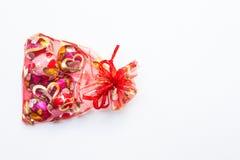 Шоколад в форме сердц в красной сумке на белой предпосылке Стоковые Изображения RF