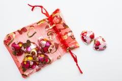 Шоколад в форме сердц в красной сумке на белой предпосылке Стоковые Фотографии RF