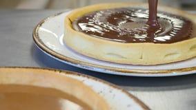 Шоколад лить на части очень вкусных свеже испеченных тортов сток-видео