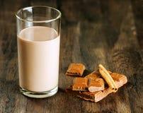 Шоколадное молоко с шоколадом и циннамоном на темной деревянной таблице стоковые изображения