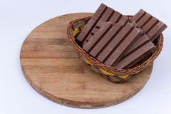 Шоколадные батончики в сплетенной корзине над белизной Стоковое Фото