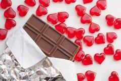 Шоколадный батончик в фольге, стеклянные сердца, Стоковые Изображения