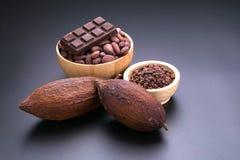 Шоколадный батончик и высушенный стручок какао, nibs какао в деревянном шаре дальше Стоковое фото RF