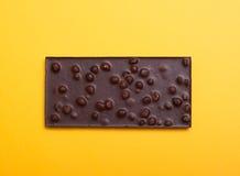 Шоколадный батончик с гайками на желтом цвете Стоковые Изображения RF