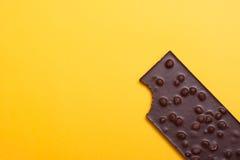 Шоколадный батончик с гайками на желтом цвете Стоковые Фотографии RF