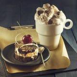 Шоколадный торт с вишнями и чашкой кофе с взбитой сливк помадка чашки круасанта кофе пролома предпосылки Стоковое фото RF