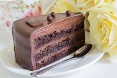 Шоколадный торт с красивым букетом желтых роз и чашки чаю Стоковое Изображение RF