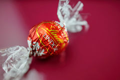 Шоколад Lindt на красной предпосылке стоковая фотография