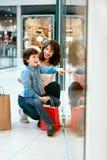 Шоппинг Молодые мать и ребенк с сумками в моле Стоковое Фото