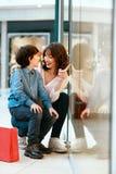 Шоппинг Молодые мать и ребенк с сумками в моле Стоковые Фото