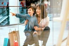 Шоппинг Молодые мать и ребенк с сумками в моле Стоковое Изображение RF