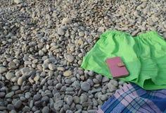 Шорты, мобильный телефон и полотенце лета аксессуар-зеленые лежа на пляже Стоковое фото RF