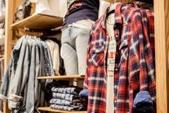 Шорты, рубашки, футболки и куртка на витрине магазина Модные одежды на полках в магазине Витрина, продажа, ходя по магазинам стоковые изображения