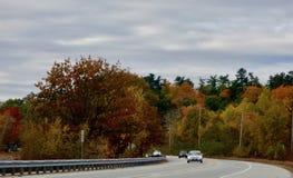 Шоссе страны в осени ярко покрасило деревья, автомобили стоковые изображения