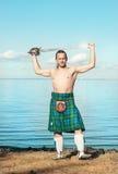 Шотландский человек с шпагой около моря Стоковые Фотографии RF