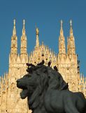 Шпили собора Duomo в милане с львом на переднем плане, который часть статуи Виктора Emmanuel II стоковое фото
