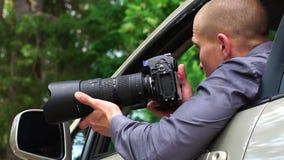 Шпионка сидит в автомобиле смотря вокруг и принимая фото видеоматериал