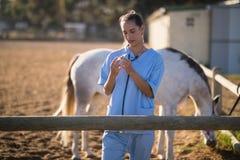 Шприц ветеринара рассматривая на амбаре Стоковая Фотография