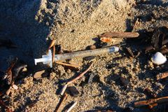 Шприц и другое грязное получившиеся отказ на пляже стоковая фотография rf