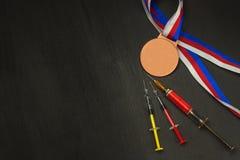 Шприц и медали давать допинг спорту Злоупотребление анаболических стероидов для спорт Анаболические стероиды разлитые на деревянн Стоковые Фото