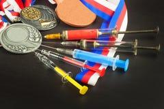 Шприц и медали давать допинг спорту Злоупотребление анаболических стероидов для спорт Анаболические стероиды разлитые на деревянн Стоковые Изображения RF